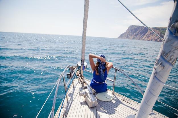Una niña en el morro del yate blanco en un tema náutico. chaqueta azul, bufanda azul y gafas de sol. en el mar abierto el océano