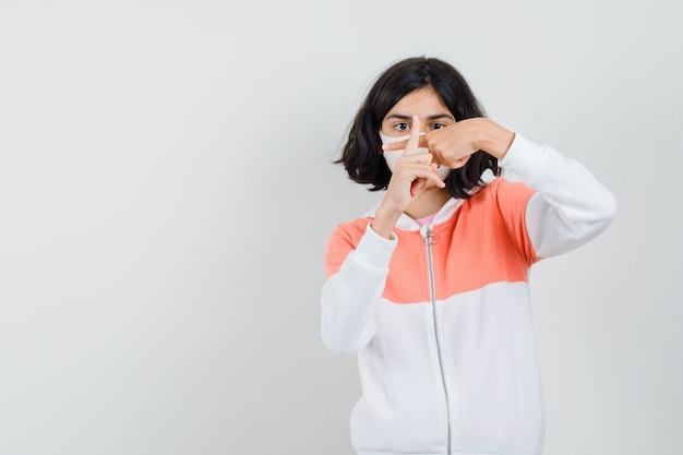 Niña mostrando cruzar los dedos formando una x en chaqueta, máscara
