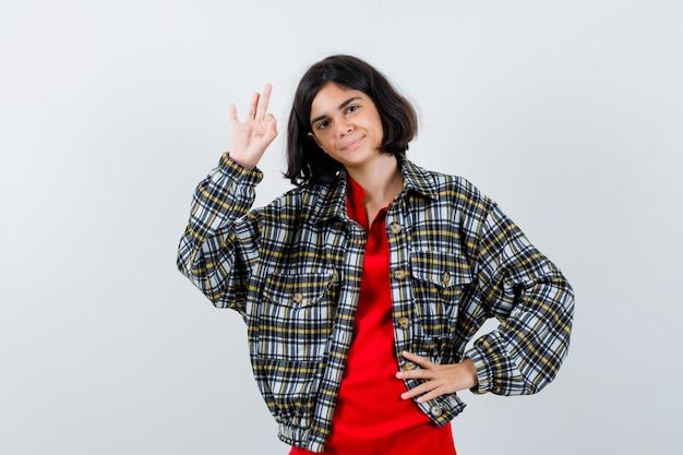 Niña mostrando gesto bien en camisa, vista frontal de la chaqueta.