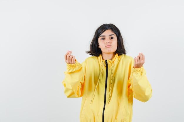 Niña mostrando gesto de dinero en chaqueta de bombardero amarilla y mirando serio,
