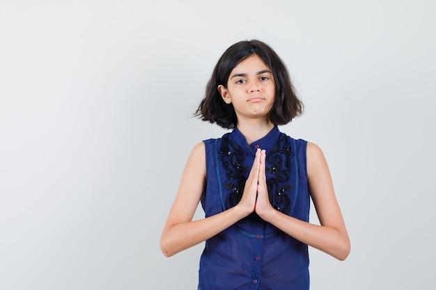 Niña mostrando gesto de namaste en blusa azul y mirando confiado