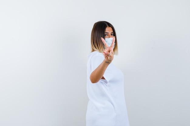 Niña mostrando gesto de paz en camiseta blanca, máscara y mirando alegre. vista frontal.