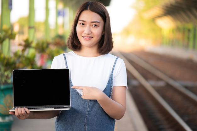 La niña está mostrando la pantalla del ordenador portátil en blanco negro