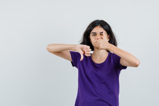 Niña mostrando los pulgares hacia arriba y hacia abajo en camiseta y luciendo sensato