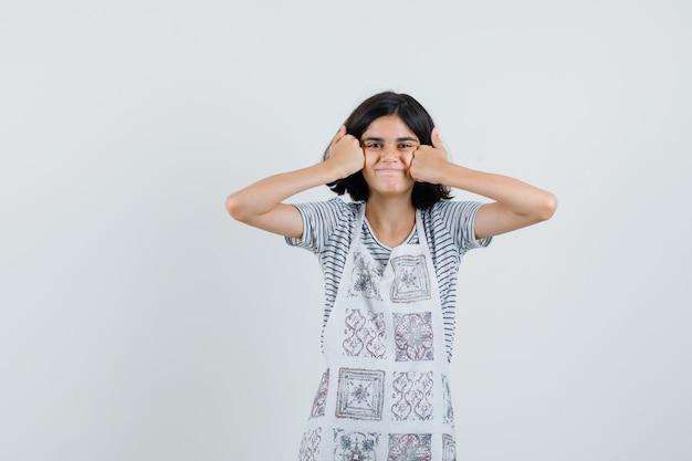 Niña mostrando los pulgares para arriba en las mejillas en camiseta, delantal y mirando contenta