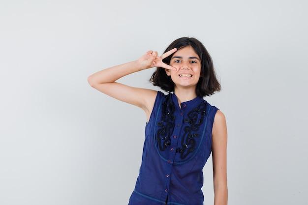 Niña mostrando el signo v cerca del ojo en blusa azul y luciendo juguetón.