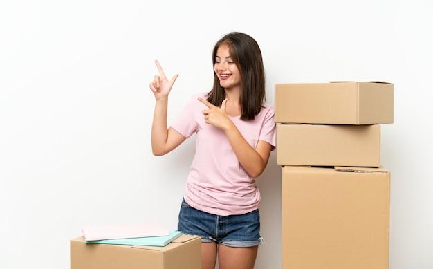Niña moviéndose en un nuevo hogar entre cajas señalando con el dedo índice una gran idea