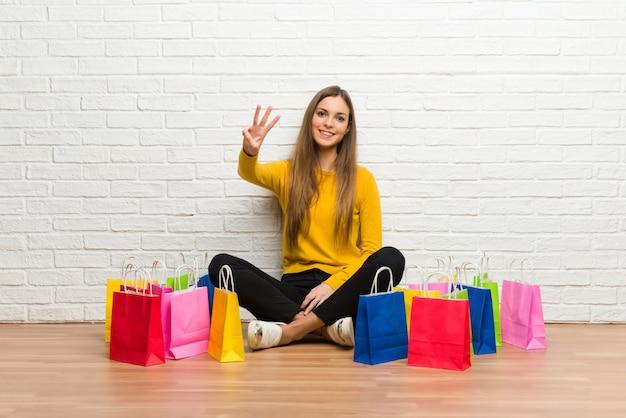 Niña con muchas bolsas de compras feliz y contando tres con los dedos