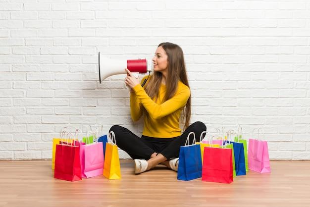 Niña con muchas bolsas de compras gritando a través de un megáfono para anunciar algo en posición lateral