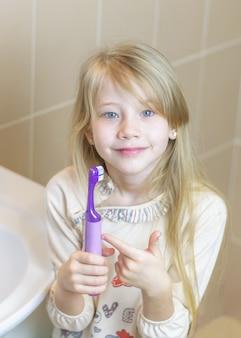 La niña muestra las delicias de un cepillo de dientes eléctrico.