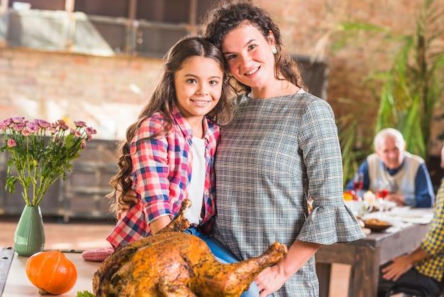 Niña y mujer abrazando cerca de pollo al horno