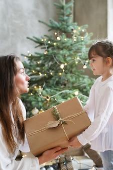 Niña y mujer con árbol de navidad y presente
