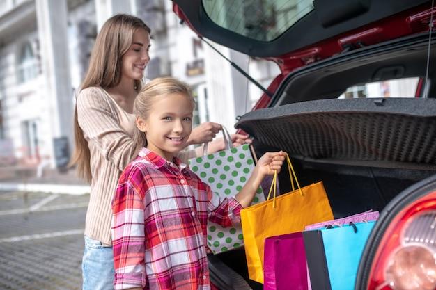 Niña y mujer joven sacando bolsas de la compra del maletero del coche