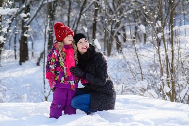 Niña y mujer mirando algo en bosque de invierno