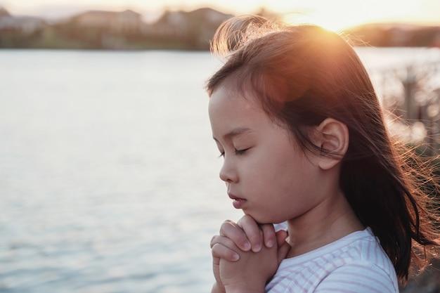Niña multicultural rezando con fondo sunflare