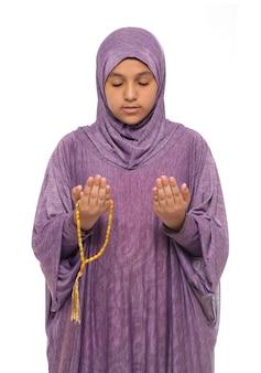 Niña musulmana rezando por alá con traje de oración y rosario, concepto de ramadán kareem