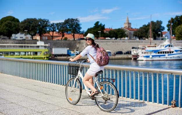 Niña muy sonriente con mochila montando bicicleta a lo largo de la acera pedregosa cercada