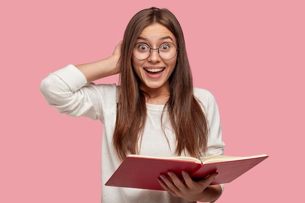 Una niña muy sonriente tiene una expresión alegre, mantiene la mano detrás de la cabeza, lleva un libro de texto rojo, sonríe ampliamente mientras lee la información necesaria, aislada sobre una pared rosa, usa gafas redondas.