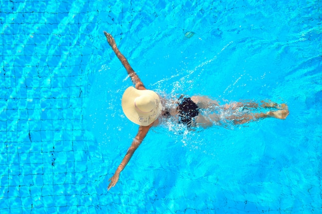 Una niña nada en la piscina. relájate en un hotel con piscina. disfrute de la natación.