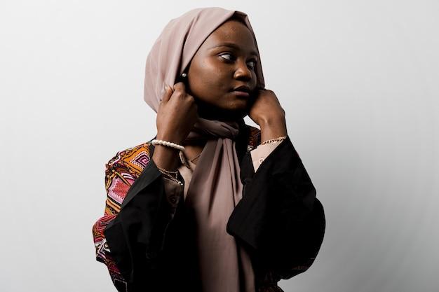 La niña negra soñadora usó hijab sonreír y regocijarse mujer musulmana feliz posando. atractiva mujer africana.