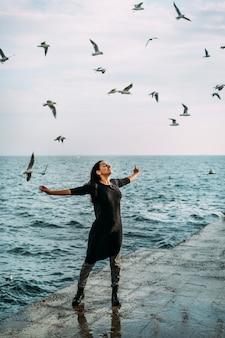 La niña de negro se para en el muelle con los brazos abiertos al sol y el viento recibe inspiración, fuerza y paz interior del alma.