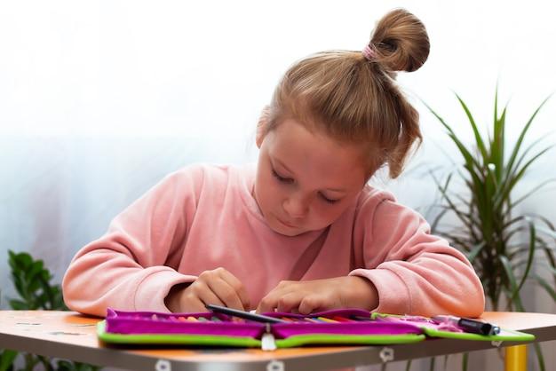 Niña niña haciendo los deberes. cuarentena
