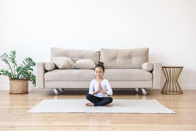 Niña niña haciendo yoga deportivo en casa en la sala de estar