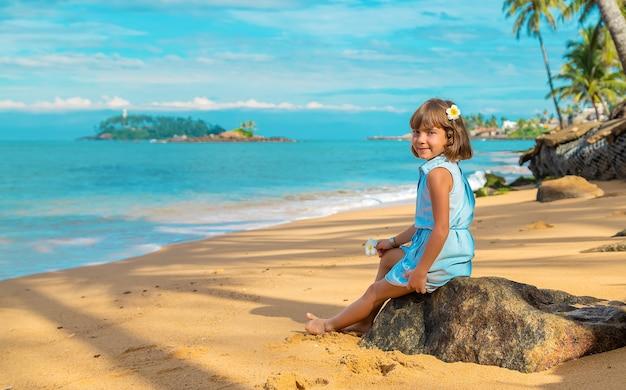 Niña niña en la playa en sri lanka. enfoque selectivo.