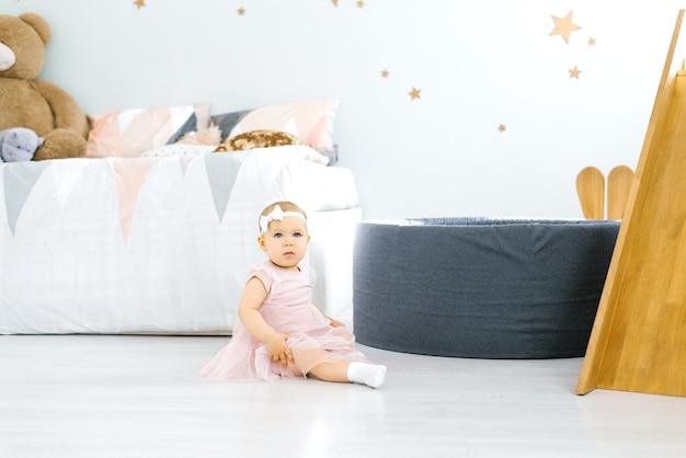 Niña niña sentada en el suelo en la habitación de los niños