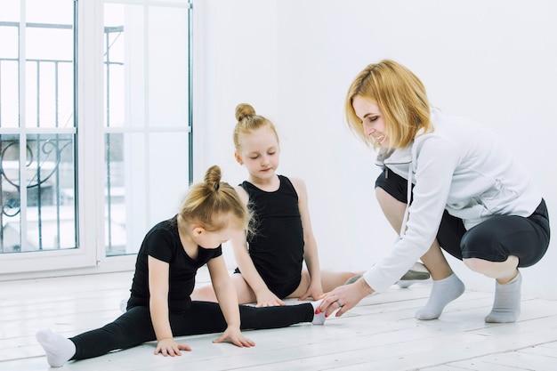 Niña niñas gimnastas y bailarina haciendo estiramientos con una entrenadora en una habitación luminosa feliz y linda
