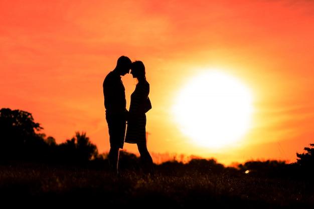 Niña y niño se abrazan en un cielo al atardecer