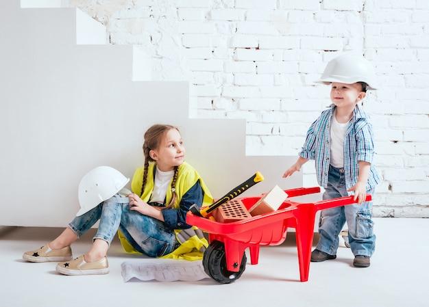 Niña y niño con carretilla en la pared blanca. construcción