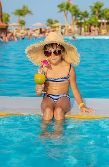 Niña niño cerca de la piscina con un cóctel