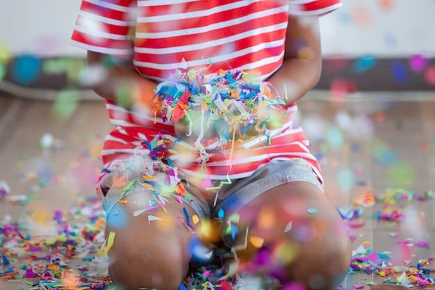 Niña niño con confeti de colores para celebrar en su fiesta