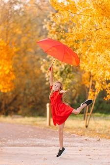 Niña niño feliz se ríe bajo el paraguas rojo