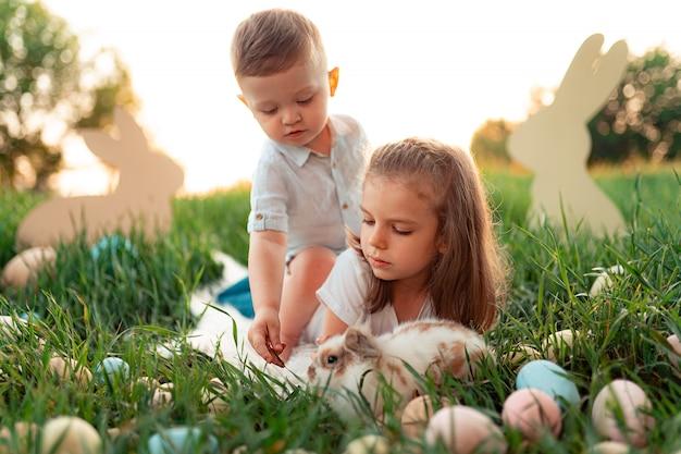 Niña y niño juegan con el conejo rodeado de huevos de pascua