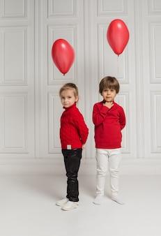 Una niña y un niño se paran y sostienen globos rojos sobre un fondo blanco con una copia del espacio