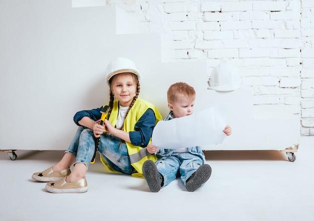 Niña y niño en la pared blanca. construcción