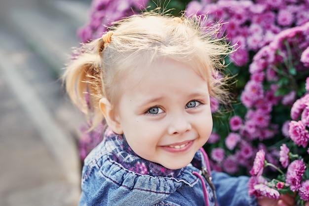 Niña niño en un parque cerca de una cama de flores de crisantemos en otoño