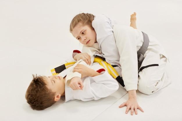 Niña y niño peleando en el piso