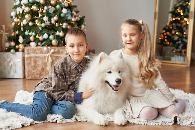 Niña y niño con perro samoyedo en navidad