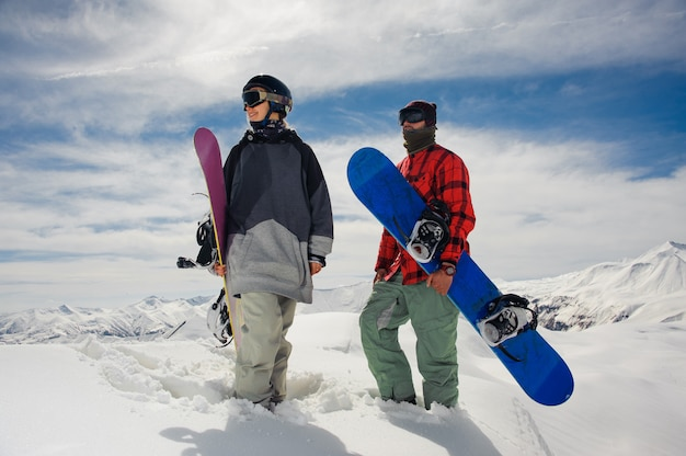 Niña y niño de pie en las montañas con tablas de snowboard