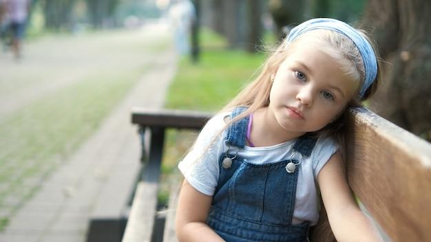 Niña niño serio sentado solo en un banco en el parque de verano.