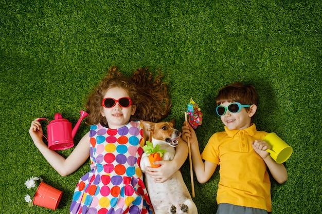 Niña y niño, y su perro tumbado en la hierba verde.