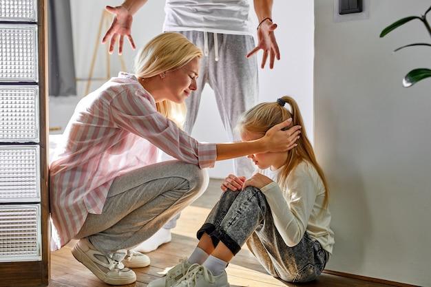 La niña niño sufre peleas entre los padres de la familia en el hogar, la mujer y el hombre discuten en presencia de la hija