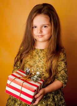 Niña niño vestido sosteniendo un regalo en la mano sobre un fondo amarillo