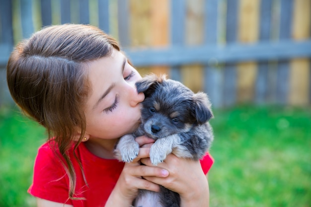Niña de los niños besando a su perrito chihuahua perrito