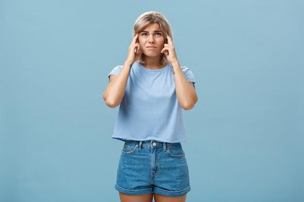 La niña no puede concentrarse escuchando ruidos fuertes que vienen de arriba, frunciendo el ceño, sintiendo intenso e insatisfecho, cerrando los oídos con los dedos índices mirando hacia arriba mientras se queja de un sonido horrible sobre la pared azul