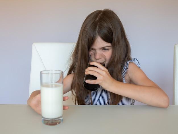Una niña no quiere beber leche, pero elige un refresco de coca cola. concepto de alimentación saludable y no saludable