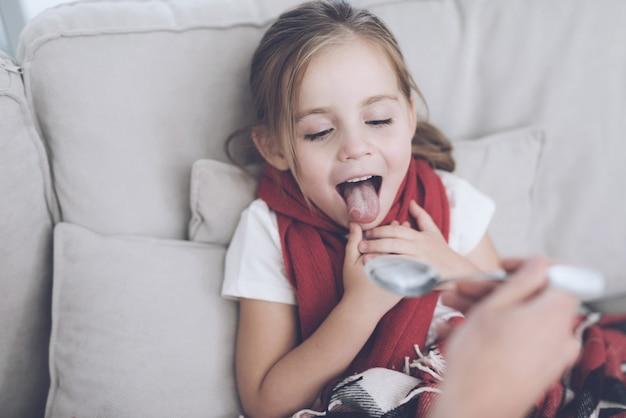 La niña no quiere tomar jarabe.